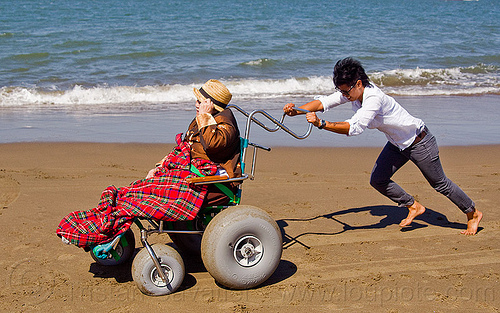 granddaughter pushing her grandma's beach wheelchair on the beach, beach wheelchair, blanket, chinese, crissy field beach, family, grandma, grandmother, jenn, ocean, old woman, pushing, rolling, sand, sea, senior, straw hat, water, women