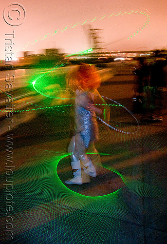 green laser hula hoop light patterns, green laser, islais creek promenade, laser hoop, laser hula hoop, night, superhero street fair, woman