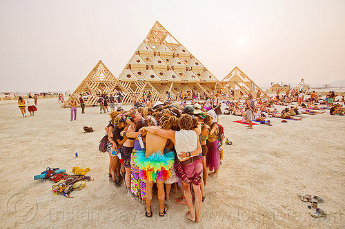 group hugging at handfasting ceremony near pyramid - burning man 2013, burning man, handfasting, temple of whollyness, wedding, wooden pyramid