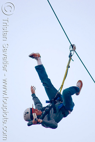 guy shooting a video on the zip-line over san francisco, adventure, blue sky, cable line, cables, camcorder, camera, embarcadero, hanging, helmet, man, mountaineering, moving fast, shooting, speed, steel cable, trolley, tyrolienne, upside-down, urban, video, zip line, zip wire