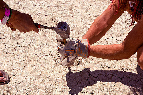 hammering a rebar - burning man 2012, arms, burning man, cracked mud, desert, drought, dry mud, earth, ground, hammer, hammering, hands, jillian, leather gloves, playa, rebar, sari, soil