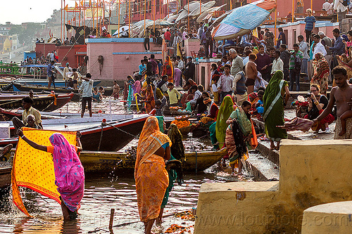 hindu bathing on the ghats of varanasi (india), backloght, crowd, ganga river, ganges river, ghats, hindu, hinduism, holy bath, holy dip, mooring, people, river bank, river bath, river bathing, river boats, sarees, sari, varanasi, water, women