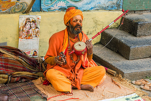 hindu devotee singing mantra and playing musical instrument (nepal), baba, beard, bhagwa, cross-legged, hindu, hinduism, kathmandu, maha shivaratri, man, musical instrument, pashupatinath, playing music, sadhu, saffron color, sitting, tilak