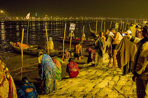 hindu pilgrims bathing in the ganges river at the sangam at night - kumbh mela 2013 (india), crowd, fence, ganga, ganges river, hindu pilgrimage, hinduism, holy bath, holy dip, india, maha kumbh mela, men, nadi bath, night, paush purnima, pilgrims, ritual bath, river bank, river bathing, river boats, sand bags, street lights, triveni sangam, women, wooden poles