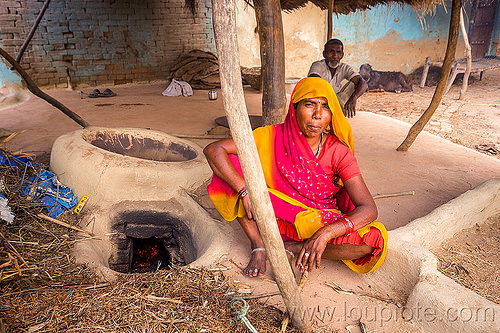 hindu woman sitting near mud stove, adobe floor, cross-legged, earthen floor, fireplace, india, khoaja phool, kitchen, man, sari, sitting, village, woman, wood stove, खोअजा फूल