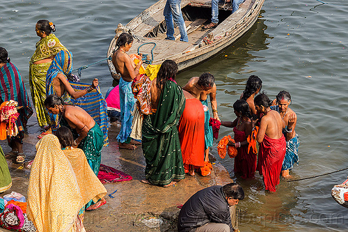 hindu women bathing in the ganges river in varanasi (india), ganga river, ganges river, ghats, hindu, hinduism, holy bath, holy dip, river bank, river bath, river bathing, river boat, sarees, saris, varanasi, water, women