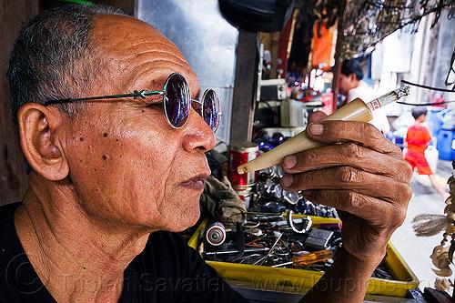 horn cigarette holder, cigarette holder, hand, horn, java, jogja, jogjakarta, man, market, smoker, smoking, street vendor, sunglasses, yogyakarta