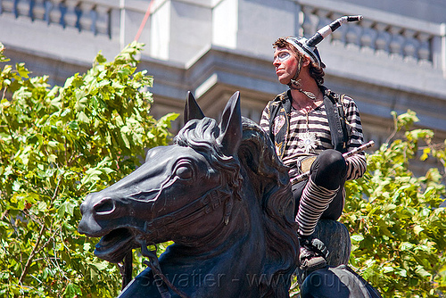 horse head sculpture, costume, faerie freedom village, gay pride festival, horns, horse head, horse riding, horseback riding, man, monument, sculpture, statue, striped