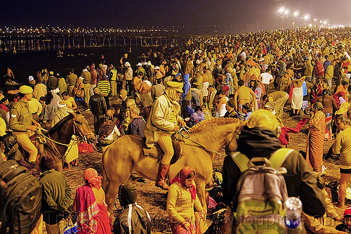 horse police patrolling the crowd of hindu pilgrims gathering at kumbh mela 2013 (india), cops, crowd control, fence, ganga river, ganges river, hindu, hinduism, holy bath, holy dip, horse riding, horseback riding, kumbha mela, law enforcement, maha kumbh mela, men, mounted police, night, paush purnima, pilgrims, police horses, police officers, reflections, ritual bath, river bank, river bath, river bathing, street lights, triveni sangam, water, women, yatris