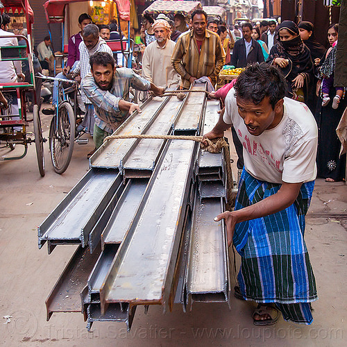 I-beam steel rails rolled on cart in street (india), construction, crowd, delhi, i-beams, india, men, rope, roped, steel beams, workers
