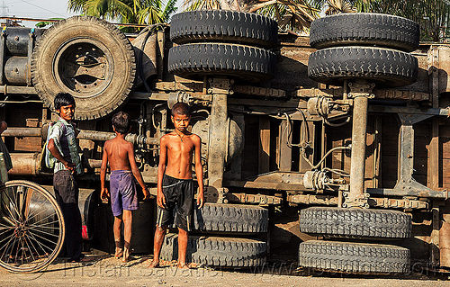 indian boys near underbelly of overturned truck (india), accident, children, crash, lorry, people, road, rollover, standing, tata, tata motors, traffic accident, truck accident, wheels, wreck
