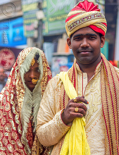indian wedding - proud groom holding bride in tow like a trophy, bride, couple, dressed-up, gold jewelry, groom, hand mehndi, headdress, headwear, indian wedding, man, nose piercing, nostril piercing, piercing jewelry, scarf, standing, street, traditional, turban, varanasi, woman