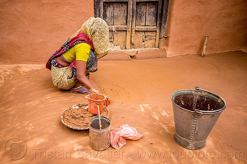indian woman making earthen floor in house, adobe floor, clay, construction, earthen floor, ground, house, khoaja phool, metal bucket, mud, spreading, village, woman, working, खोअजा फूल
