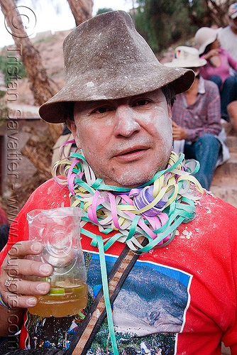 indigenous man celebrating and drinking - carnaval de tilcara (argentina), andean carnival, carnaval, confettis, drink, drinking, hat, man, noroeste argentino, quebrada de humahuaca, serpentine throws, talk powder, tilcara
