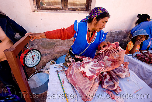 indigenous woman selling llama meat, argentina, butcher, llama meat, meat market, meat shop, merchant, noroeste argentino, quebrada de humahuaca, raw meat, street seller, tilcara, vendor, weigh scale, weighting scale, woman