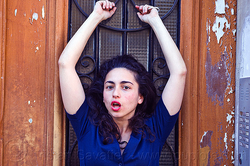 italian girl with arms raised, brunette, curly hair, dilve, hands, house door, ironworks, italian woman, long hair, paris, red lipstick