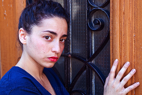 italian girl with somber face, brunette, curly hair, dilve, door window, hand, house door, ironworks, italian woman, long hair, paris, red lipstick