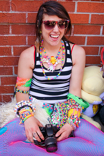 kandi raver girl with camera, beads, bracelets, brick wall, camera, fishnet clothing, fishnet stockings, fishnet tights, kandi kid, kandi raver, photographer, rave fashion, sitting, woman