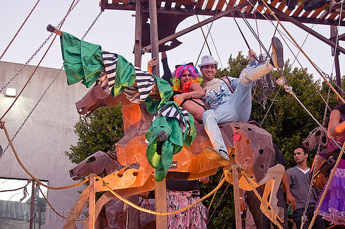 kicking leg up, a cavallo, burning man decompression, couple, horse carousel, metal horse, riding, stilter, woman