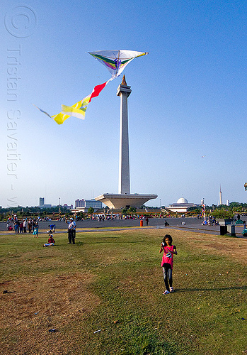 kid flying a kite near the national monument (monas) in jakarta, architecture, child, column, eid, eid ul-fitr, girl, java, medan merdeka, merdeka square, monumen nasional, park, turf