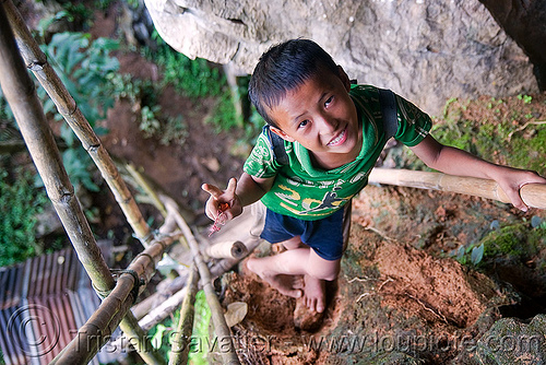 kid on bamboo ladder to cliff cave near vang vieng (laos), bamboo ladder, boy, caving, child, cliff, guide, kid, laos, natural cave, peace sign, spelunking, vang vieng