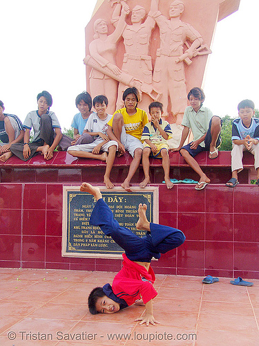 kids break-dancing in front of communist monument - vietnam, boys, break dance, break dancing, children, communism, kids, memorial, monument, phan thiet, victory, vietnam