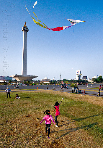 kids flying a kite near the national monument (monas) in jakarta, architecture, children, column, eid ul-fitr, flying, indonesia, jakarta, kids, kite, lawn, medan merdeka, merdeka square, monumen nasional, national monument, park