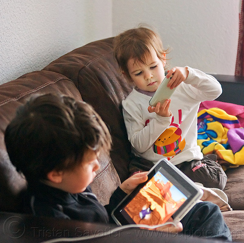 kids playing games on iPad and iPhone, boy, brother, cellphone, children, coach, ipad, iphone, kids, little girl, playing, siblings, sister, sitting, tablet computer, video game