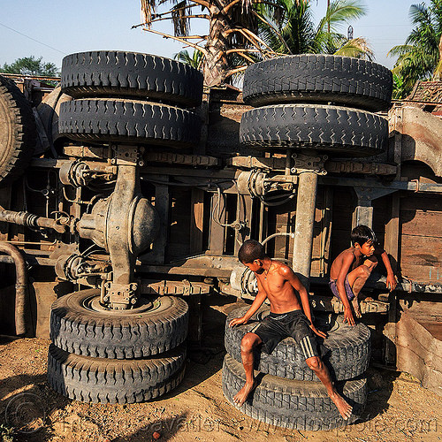 kids playing on overturned truck (india), boys, children, crash, dead axle, differential, kids, lorry, overturned truck, playing, road, rollover, sitting, tata motors, traffic accident, truck accident, underbelly, wheels, wreck