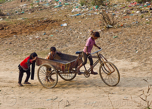 kids playing with freight tricycle (india), boy, cargo tricycle, cargo trike, children, environment, freight tricycle, freight trike, garbage, girl, kids, plastic trash, playing, pollution, pushing, riding, rubbish