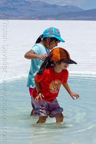 kids wading in salt pool - salinas grandes - salar (argentina), blue sky, caps, children, halite, jujuy, kids, noroeste argentino, rock salt, salar, salinas grandes, salt bed, salt flats, salt lake, salt pool, wading, water, white