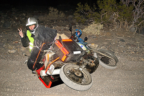 KLR 650 motorbike crash, crash, desert, dirt road, dropped, dual-sport, kawasaki, klr 650, luggage rack, lying down, mishap, motorbike touring, motorcycle accident, motorcycle helmet, motorcycle touring, night, pannier cases, panniers, peace sign, reflective tape, sand, sharon, unpaved, v sign, woman