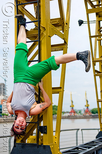 krista playing with a harbor crane, buenos aires, krista, puerto madero, upside-down, woman