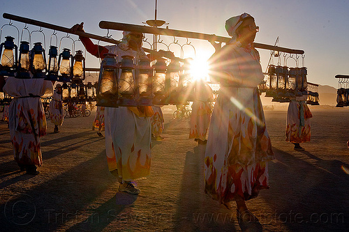 lamplighters at sunset - burning man 2012, backlight, burning man, dawn, lamp lighters, lamplighter, lens flare, petrol lamps, petrol lanterns, poles, sun, sunset
