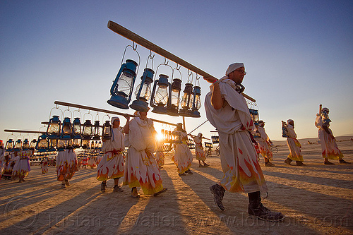 lamplighters at sunset - burning man 2013, burning man, carrying, lamplighters, petrol lanterns, poles, porters
