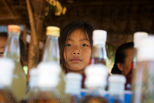laotian girl - whisky village, near pak ou caves -  luang prabang (laos), beverage, bottles, child, kid, lao whisky, lao-lao, liquor, little girl, luang prabang, pak ou caves temples, rice alcohol, rice whisky, rice wine, vodka, whisky village