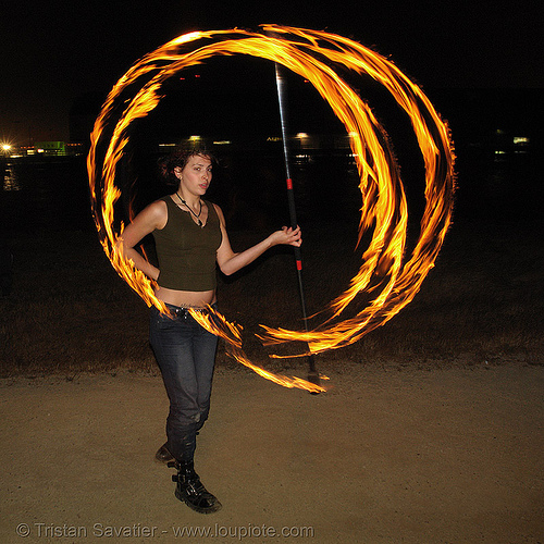 lexie spinning a fire staff, fire dancer, fire dancing, fire performer, fire spinning, flames, long exposure, night, people, spinning fire