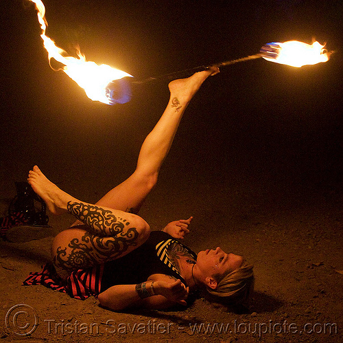 lily spinning fire staff with feet (san francisco), fire dancer, fire dancing, fire performer, fire spinning, fire staff, leg tattoo, night, spinning fire, tattooed, tattoos, woman