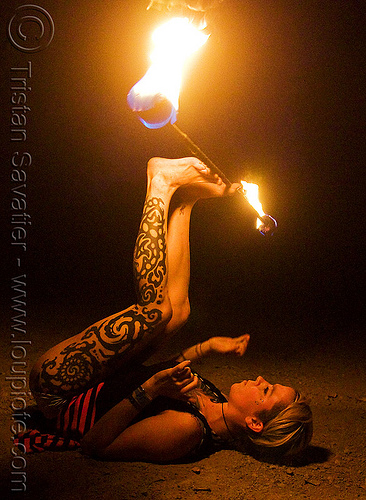 lily spinning fire staff with feet (san francisco), fire dancer, fire dancing, fire performer, fire spinning, fire staff, flames, leg tattoo, lily, long exposure, night, spinning fire, tattooed, tattoos, woman