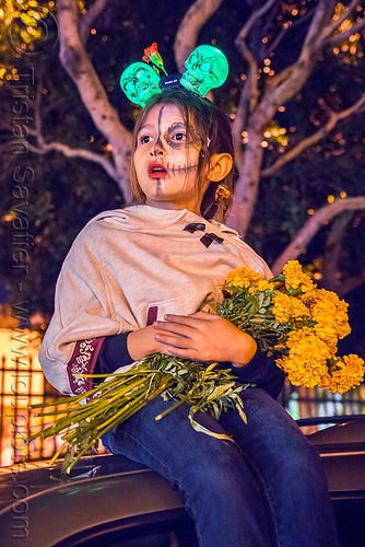 little girl holding bunch of marigold flowers - dia de los muertos, child, day of the dead, dia de los muertos, face painting, facepaint, flower bunch, flowers, green skulls, halloween, headdress, kid, little girl, marigold, night, sitting, sugar skull makeup
