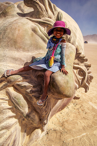 little girl on da vinci's nose - burning man 2016, art installation, burning man, child, da vinci head, giant head, kid, little girl, purple hat, sculpture