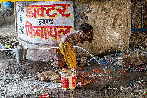 little girl washing face at water hose, bridge pillar, child, daraganj, hindu pilgrimage, hinduism, india, kid, little girl, maha kumbh mela, metal bucket, plastic pipe, plastic piping, steel bucket, washing, water hose, water pipe