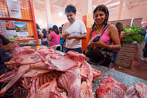 llama meat at meat market, llama meat, man, meat market, meat shop, noroeste argentino, quebrada de humahuaca, raw meat, tilcara, woman