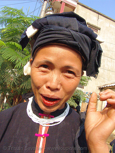 """lo lo den"" tribe woman with red lips caused by chewing betelnut - vietnam, areca nut, asian woman, betel leaf, betel nut, betel quids, betelnut teeth, black lo lo tribe, bảo lạc, cau, headdress, hill tribes, indigenous, lo lo den tribe, lá trầu, necklace, vietnam"