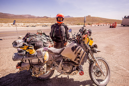 loaded KLR 650 motorcycle - burning man 2015, bags, burning man, dual-sport, dust, dusty, helmet, ims tank, kawasaki, klr 650, luggage, motorcycle touring, overloaded, rider, road, standing