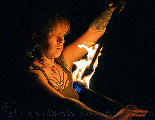 looking at fire staves - leah, fire dancer, fire dancing, fire performer, fire spinning, fire staffs, fire staves, flames, leah, night, tattooed, tattoos, woman