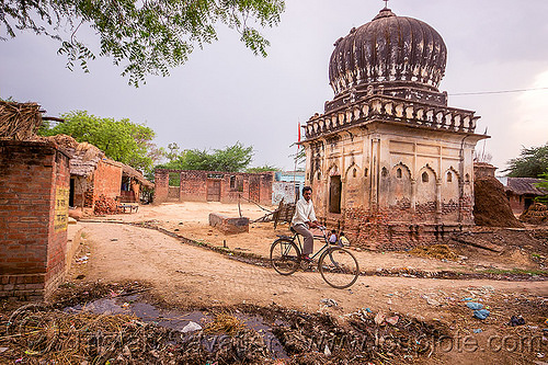 man on bicycle near old monument in indian village, bicycle, garbage, khoaja phool, man, monument, plastic trash, rubbish, shrine, temple, village, खोअजा फूल