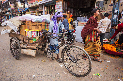 man pushing cargo tricycle with heavy load (india), bags, bearer, boxes, cargo tricycle, cargo trike, freight tricycle, freight trike, heavy, load, man, moving, pushing, sacks, sarees, sari, shops, street, transport, transportation, transporting, varanasi, walking, woman