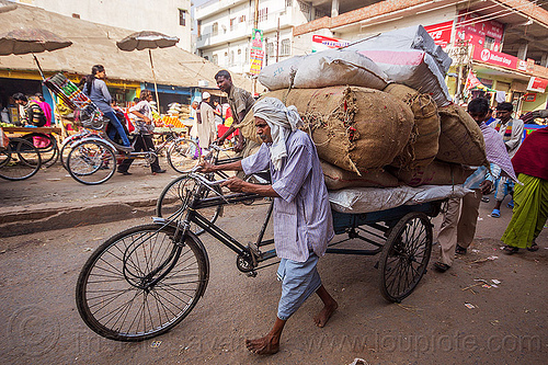 man pushing freight tricycle with heavy load (india), bags, bare foot, bearer, cargo, cargo tricycle, cargo trike, freight trike, moving, people, sacks, street, transport, transportation, transporting, varanasi, walking