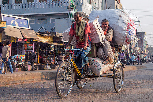 man riding with large sacks of freight on cycle rickshaw (india), bags, cargo, cycle rickshaw, freight, india, load, men, moving, riding, sacks, transport, transportation, transporting, varanasi